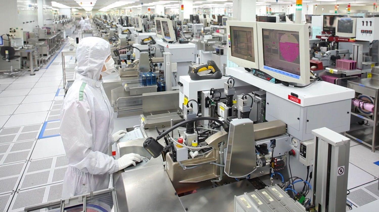 Un miembro del equipo de producción de Micron usa una gorra, overoles y máscara especiales para ayudar a mantener la sala limpia libre de partículas