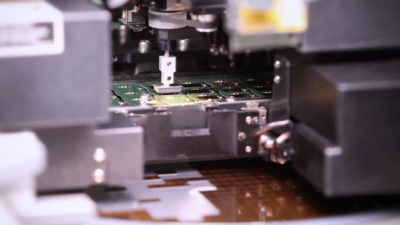 Una máquina toma un chip del alimentador y lo coloca sobre el PCB