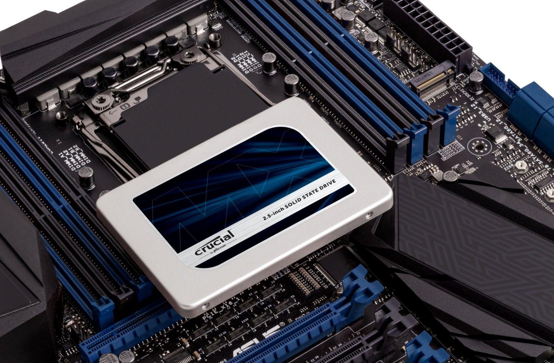 Una SSD Crucial en una motherboard de computadora abierta mostrando cómo puede actualizar su disco de almacenamiento en una computadora antigua