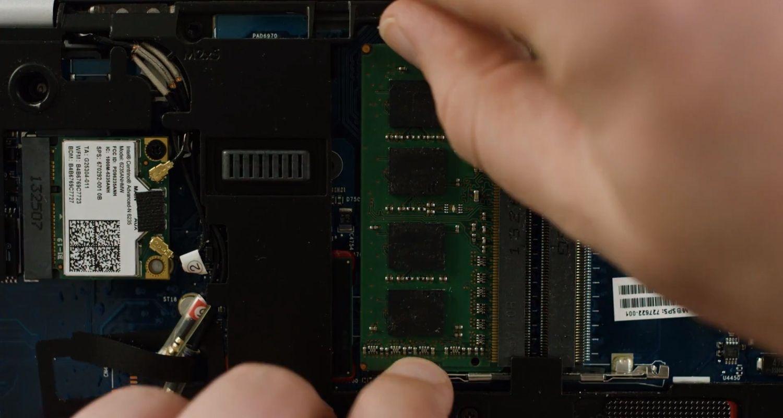 Persona sacando un módulo de memoria RAM desde adentro de la computadora portátil