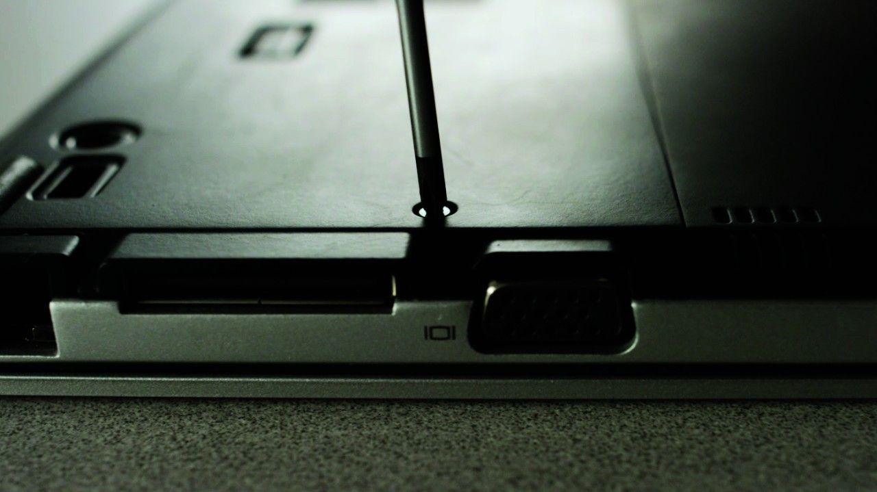 Destornillador eliminando tornillo de la parte posterior de la computadora portátil