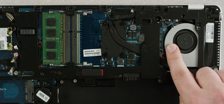 El dedo de una persona toca una superficie de metal sin pintar en la parte inferior expuesta en una computadora portátil para la descarga de electricidad estática.